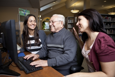 social worker: Volunteers teaching a senior how to use a computer