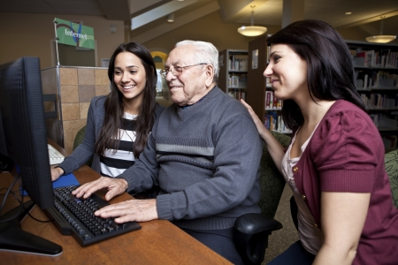 assisted living: Volunteers teaching a senior how to use a computer