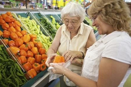 ayudando: Voluntarios ayudando a senior con sus compras  Foto de archivo