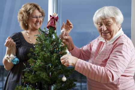 decorating christmas tree: Volunteer helping senior decorate her Christmas Tree
