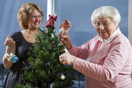 Vrijwilligers helpen senior versieren haar kerstboom