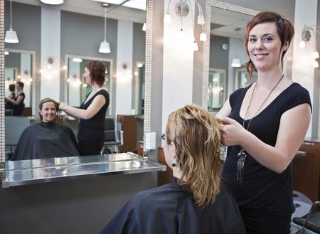 Stylist: La mujer cortarse el pelo en un salón de belleza Foto de archivo