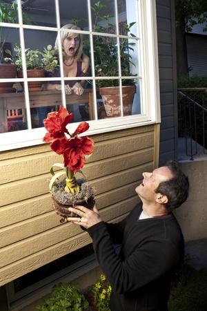 serenata: Stalker rom�ntico ofreciendo flores a Lump fuera mujer Foto de archivo