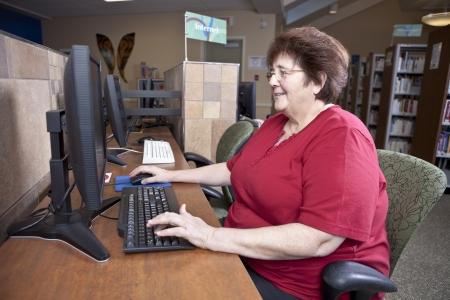 mujeres mayores: Mujer utilizando equipo de biblioteca Foto de archivo