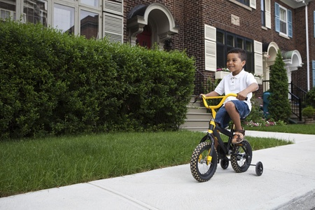 training wheels: Young boy riding his first bicycle with training wheels (horizontal)