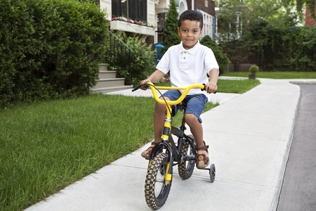 Young boy riding his first bicycle with training wheels (horizontal) photo