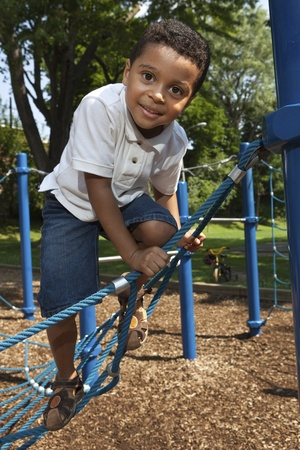 jungle gyms: Young boy playing at a park