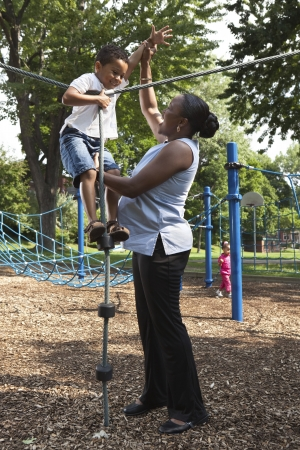 single moms: Mother and son playing at a park