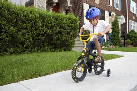 training wheels: Young boy with helmet riding his first bicycle with training wheels