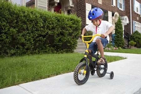 有盔甲的年轻男孩骑他的与训练轮子的第一自行车