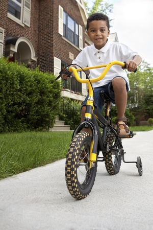 neighbourhood: Young boy riding his first bicycle with training wheels (vertical)
