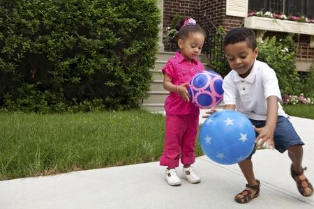 hermanos jugando: Ni�os jugando fuera Foto de archivo