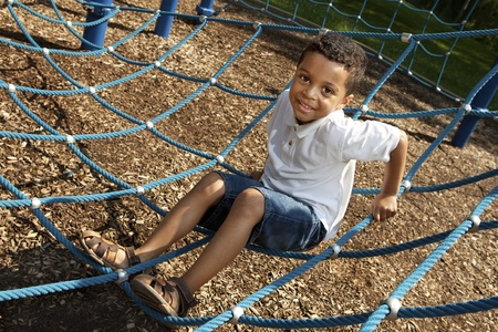 jungle gym: Young boy playing at a park