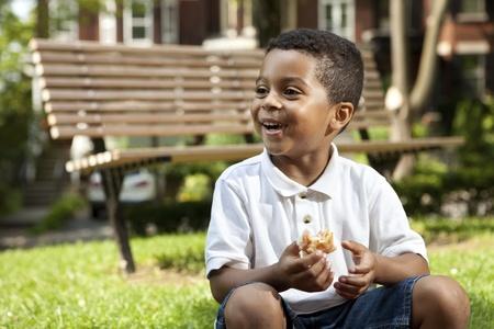 niños comiendo: Niño comiendo en un parque Foto de archivo