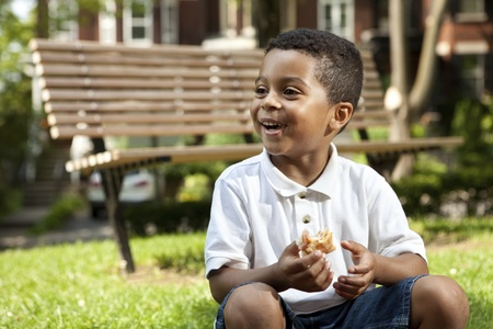 children eating: Young boy eating at a park