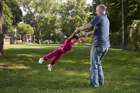 Father and daughter spinnig at the park photo