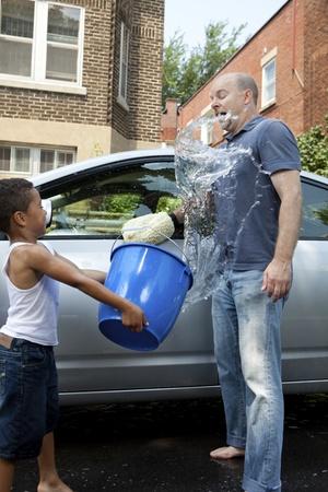 emmer water: Vader en zoon wassen van een auto horseplay spatten
