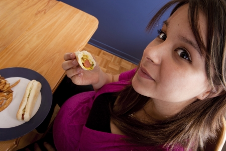 Young pregnant woman eating junk food  photo