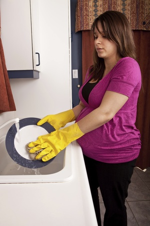 Young Pregnant Woman washing dishes  photo