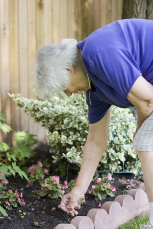 bending over: Backpain - Senior woman flower garden