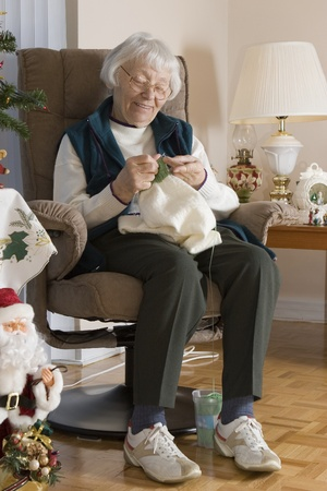 seniors homes: Senior woman knitting vertical  Stock Photo