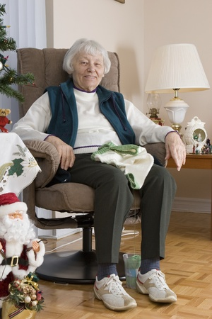 social security: Senior woman knitting vertical  Stock Photo