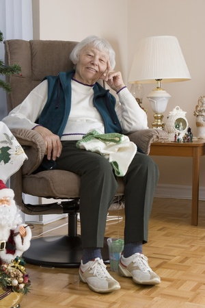 social apartment: Senior woman knitting vertical  Stock Photo