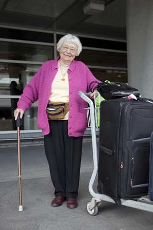 baggage train: Senior woman travelling with luggage  Stock Photo