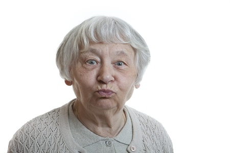 grimacing: Senior woman studio portrait grimacing blowing cheeks  Stock Photo