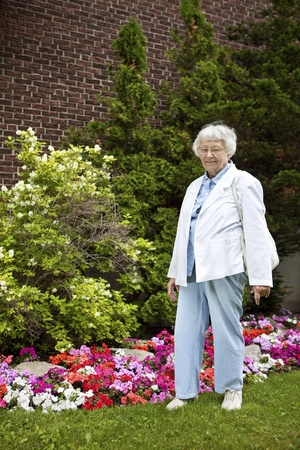 apartment living: Senior woman with garden and building background  Stock Photo