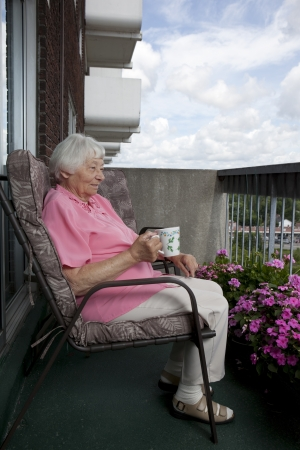 balcony: Senior woman on a coffee break  Stock Photo