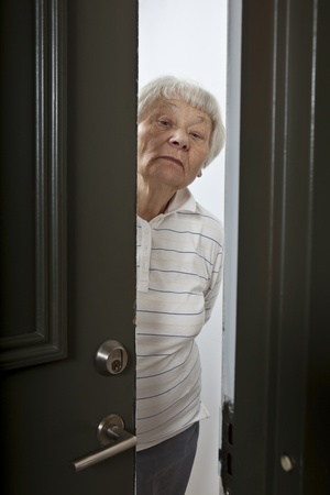 opening door: Annoyed senior woman opening front door  Stock Photo