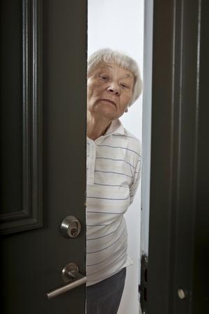 abriendo puerta: Molesto mujer mayor apertura de la puerta delantera