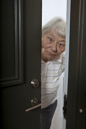 answering: Senior woman opening front door