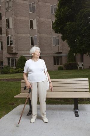 バス停で待っている年配の女性