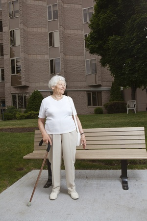 Senior vrouw te wachten bij een bushalte Stockfoto