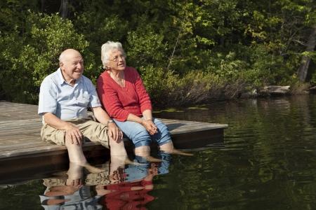 jubilados: Pareja de ancianos disfrutando de un día en el lago