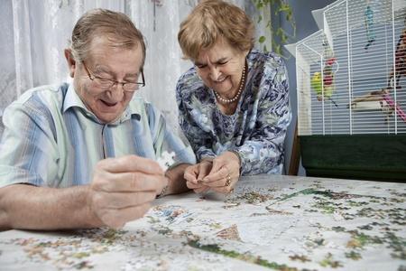 actividades recreativas: Matrimonios de edad trabajando en un rompecabezas Foto de archivo