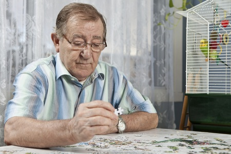 Senior man working on a puzzle  Stock Photo - 11134054