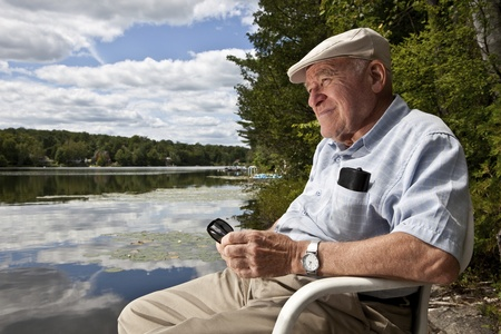 serene people: Senior man enjoying a day at the lake  Stock Photo
