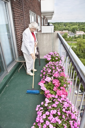 assisted living: Senior woman brooming her balcony