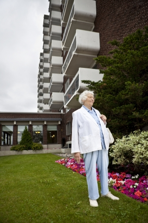 old building facade: Senior woman in front of apartment building