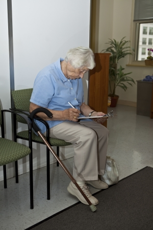 questionnaire: Senior woman filling out forms at the doctor`s office