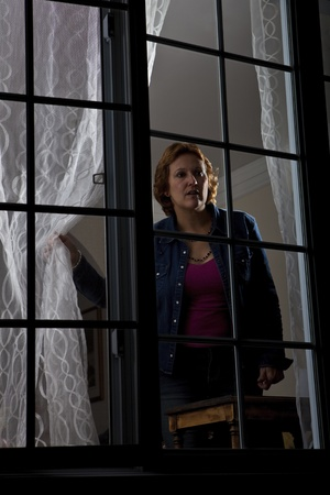 paranoid: Woman looking out from behind a window