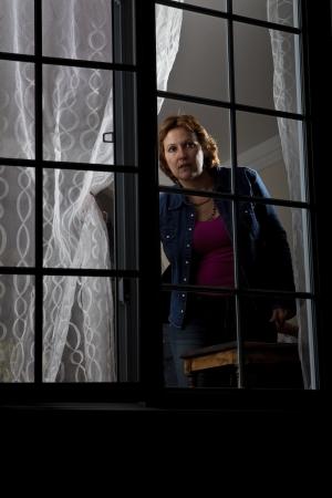 여자는 창문 뒤에서보고 스톡 콘텐츠