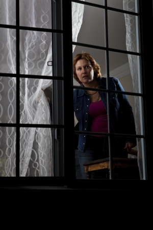 burglary: Woman looking out from behind a window