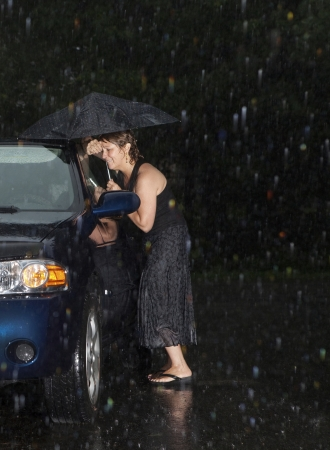 slot met sleuteltje: Vrouw uitgesloten van haar auto in de regen Stockfoto
