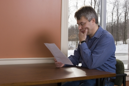 Businessman reading a letter at the library (winter)