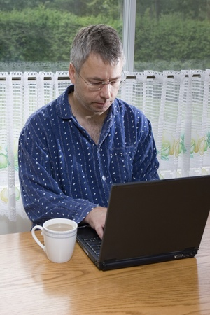 telecommuter: Businessman working from home in pajamas (SUMMER)
