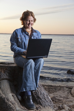 teleworking: Happy businesswoman teleworking (beach)